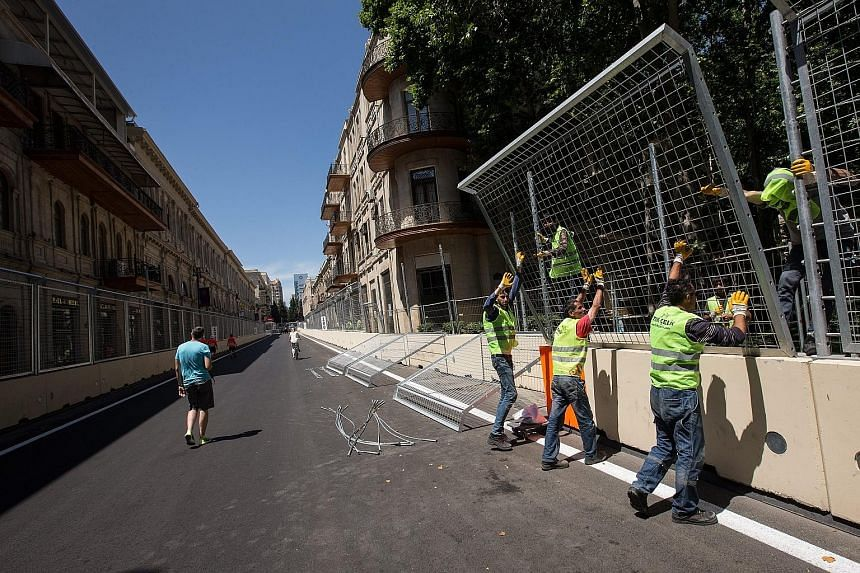 Workers fixing fences at the Baku street circuit in the Azerbaijan capital. The European Grand Prix returns after a three-year break as the former Soviet republic makes its debut on the F1 calendar.