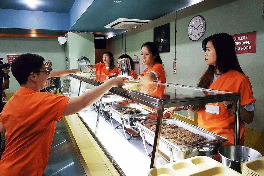 Women in orange jumpsuits (above) serve the meals at the Singapore prison-themed dining event.