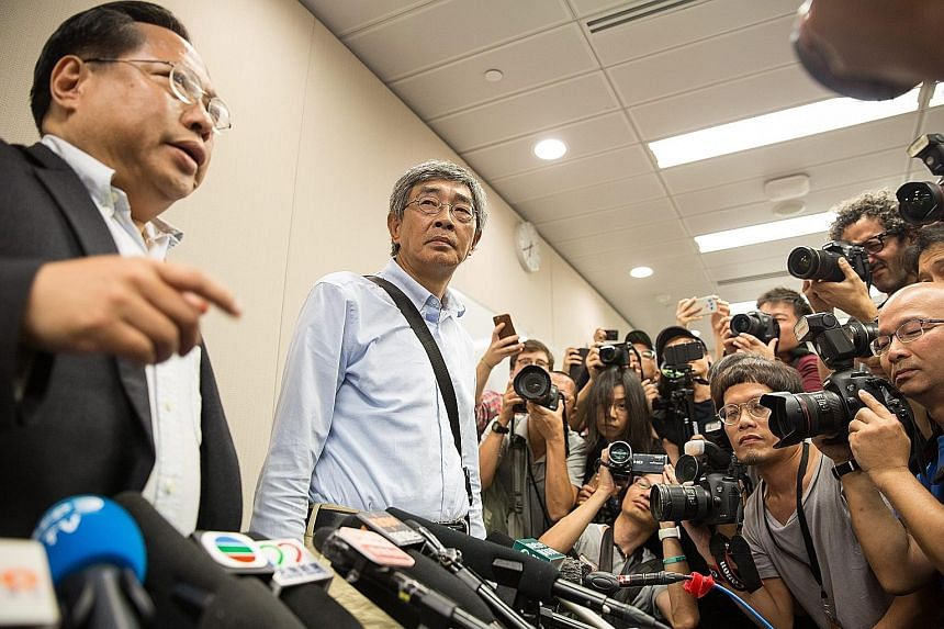 Mr Lam (centre), one of five people associated with Causeway Bay Bookstore who went missing last year, with Democratic Party lawmaker Albert Ho at a news conference held at the party's office in the Legislative Council complex in Hong Kong yesterday.