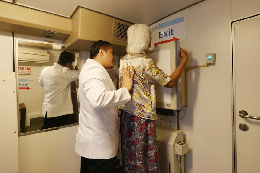 A SATA staff helps a resident of Block 203 Ang Mo Kio Ave 3 take an X-ray in a medical services bus at the carpak on June 16.
