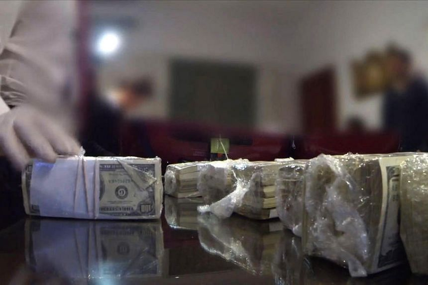 A screengrab from a video by the Argentinian police showing money, weapons, jewels and other objects seized from former minister Jose Lopez.