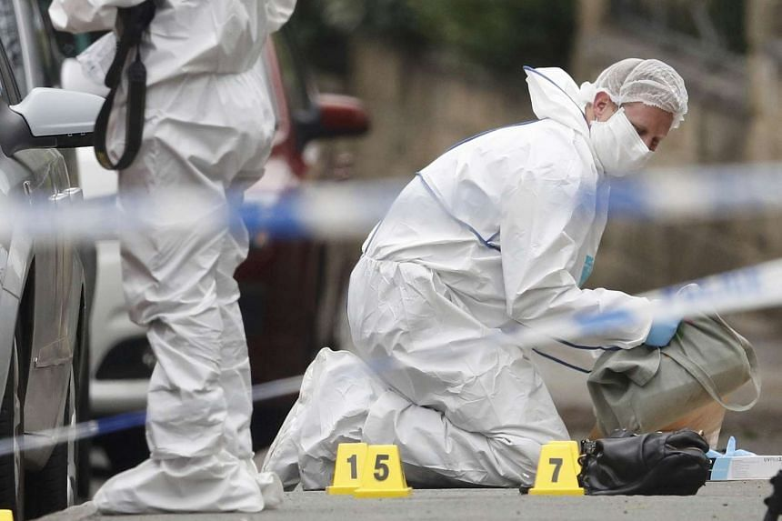 A forensic police officer collects a bag from the ground behind a police cordon in Birstall near Leeds, on June 16.