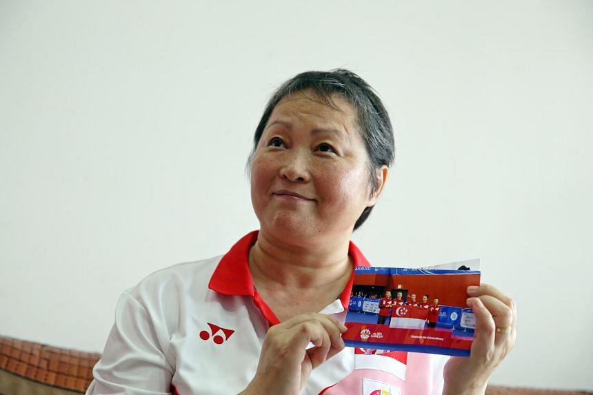 Ms Zhu holding up a photo of her gymnasts during the 2015 SEA Games.