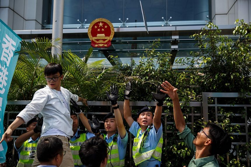 A pro-democracy group Demosisto member (right) throws a placard towards the Chinese Liaison office during a protest in Hong Kong on June 17.