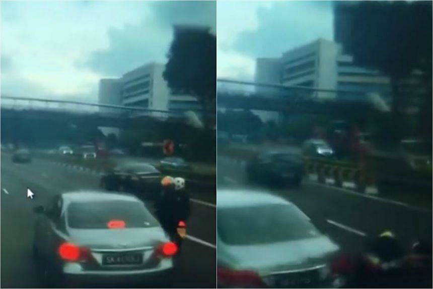 The Toyota Camry is filmed swerving into the motorcycle, with the impact knocking the motorcyclist and his pillion rider to the ground.