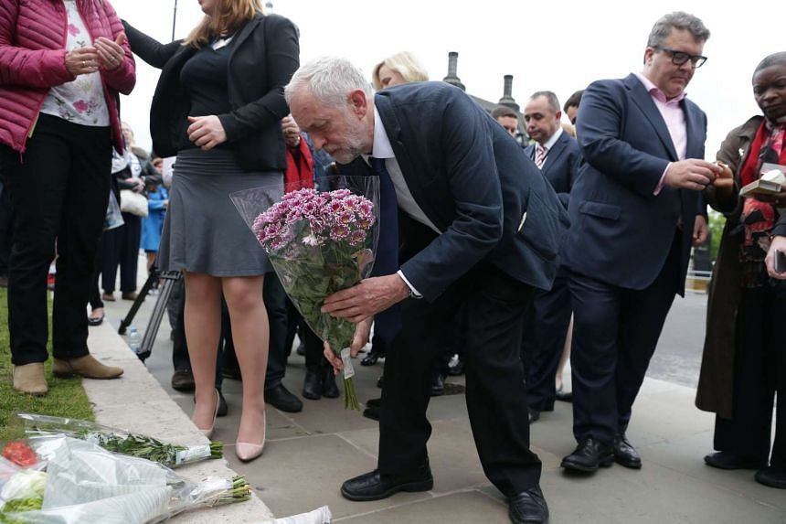 Labour leader Jeremy Corbyn (centre) lays a wreath as he attends a vigil to slain Labour MP Jo Cox in Parliament square in London on June 16, 2016.
