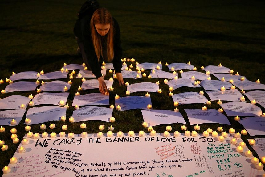 A woman places candles in tribute to Labour Party MP Jo Cox, who was shot dead in the street in northern England, on Parliament Square in London, Britain, on June 16.