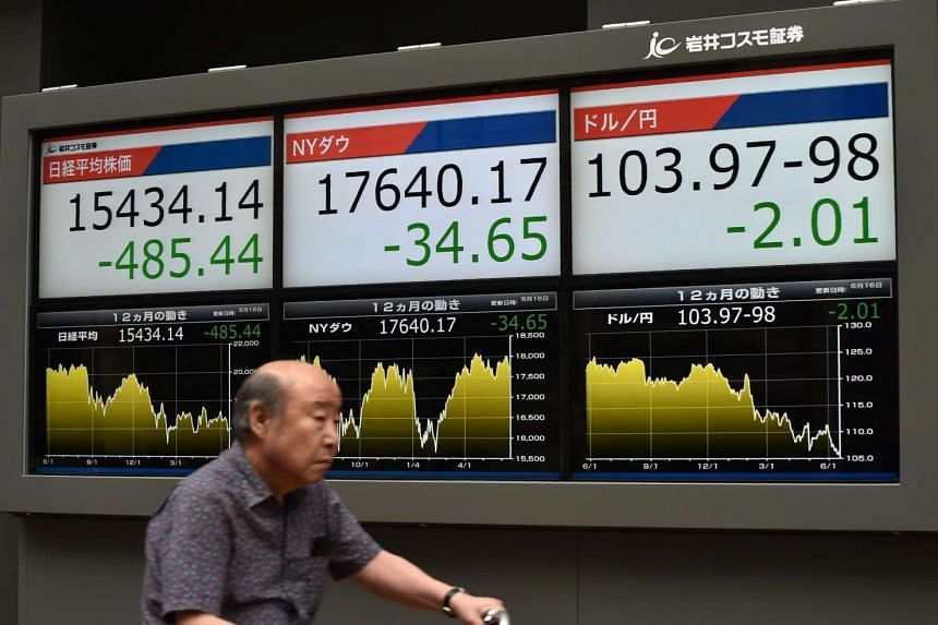 A man cycling past an electronic forex board in Tokyo on June 16.