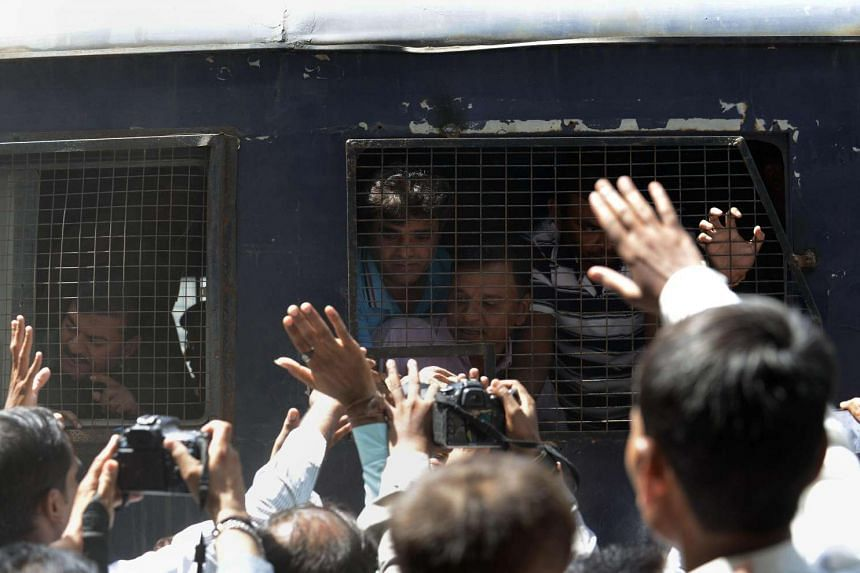 Indian Hindus convicted of involvement in fatal riots are surrounded by media and relatives as they are taken in a police van in Ahmedabad, on June 9, 2016.