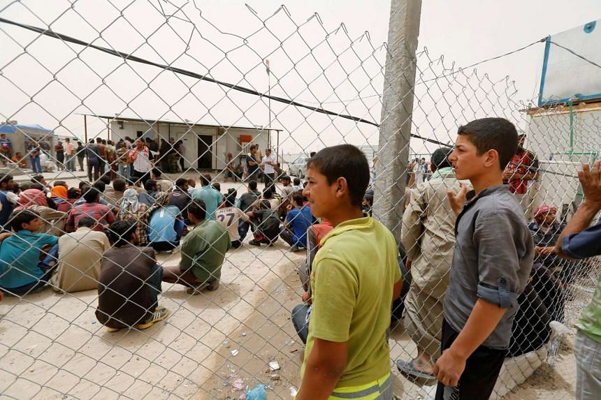 Boys who fled from Falluja look for their relatives who are waiting for security checks from tribal fighters, at a refugee camp in Ameriyat Falluja, on June 16, 2016.