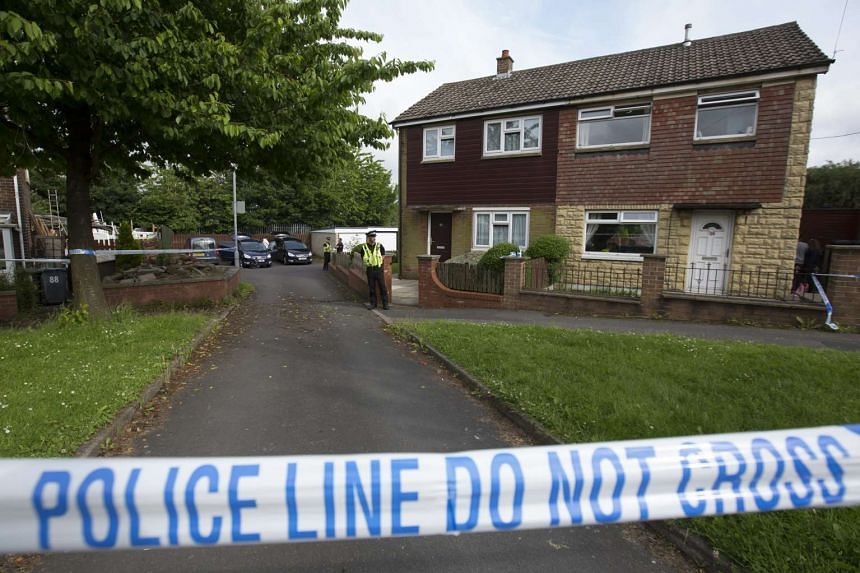 A police tape cordons off a road as officers investigate at the home of the suspect.