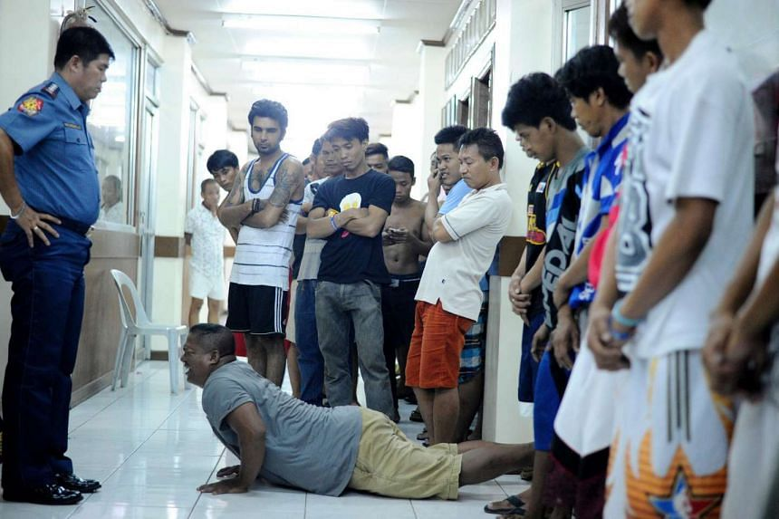 Men who violated a liquor ban are made to do push-ups by police officers in Manila on May 28.