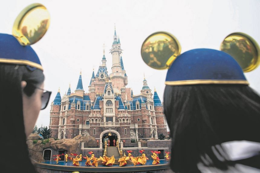 Women wearing Mickey Mouse ears watch the opening ceremony of the Shanghai Disney Resort in Shanghai on June 16.