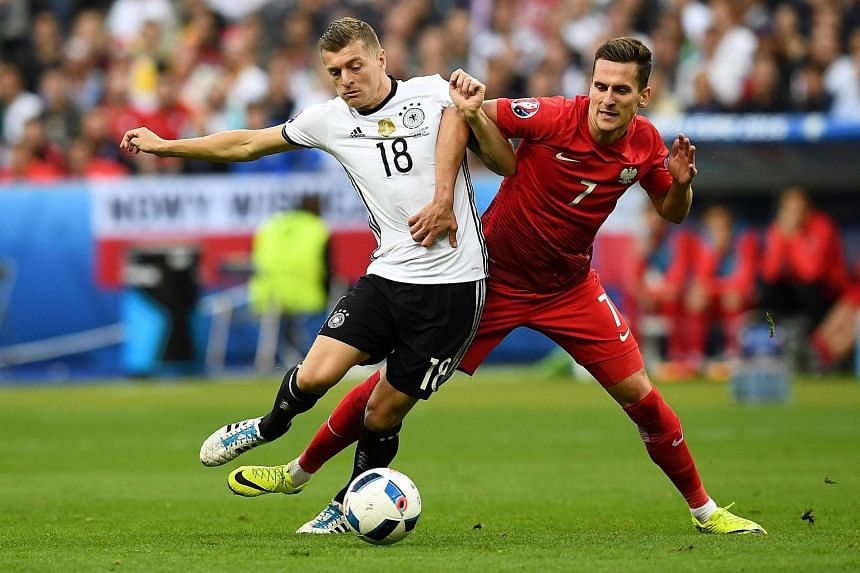Germany's Toni Kroos (left) vying for the ball against Poland's Arkadiusz Milik.
