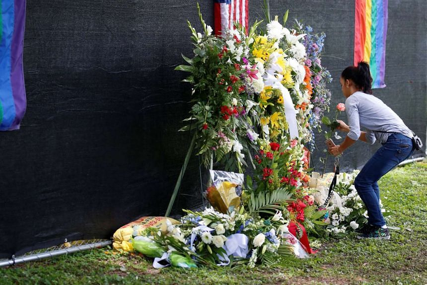 A mourner places a flower near the grave of Pulse night club shooting victim Anthony Luis Laureano Disla after his funeral in Orlando, Florida, US on June 17, 2016.