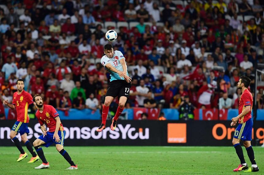 Turkey's forward Burak Yilmaz (centre) heads the ball during the Euro 2016 group D football match between Spain and Turkey at the Allianz Riviera stadium in Nice on June 17, 2016.