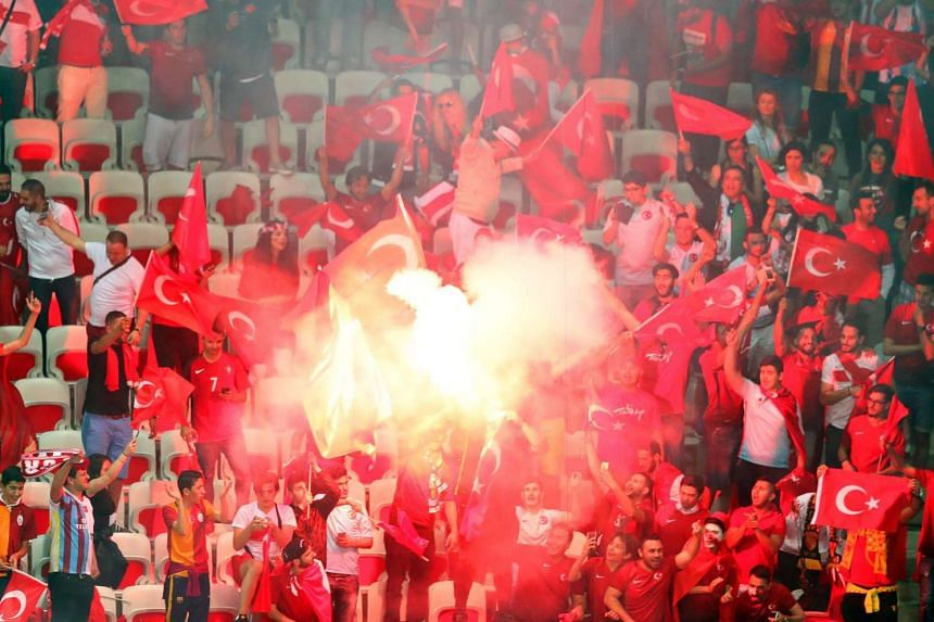 Turkish fans light flares after the match.