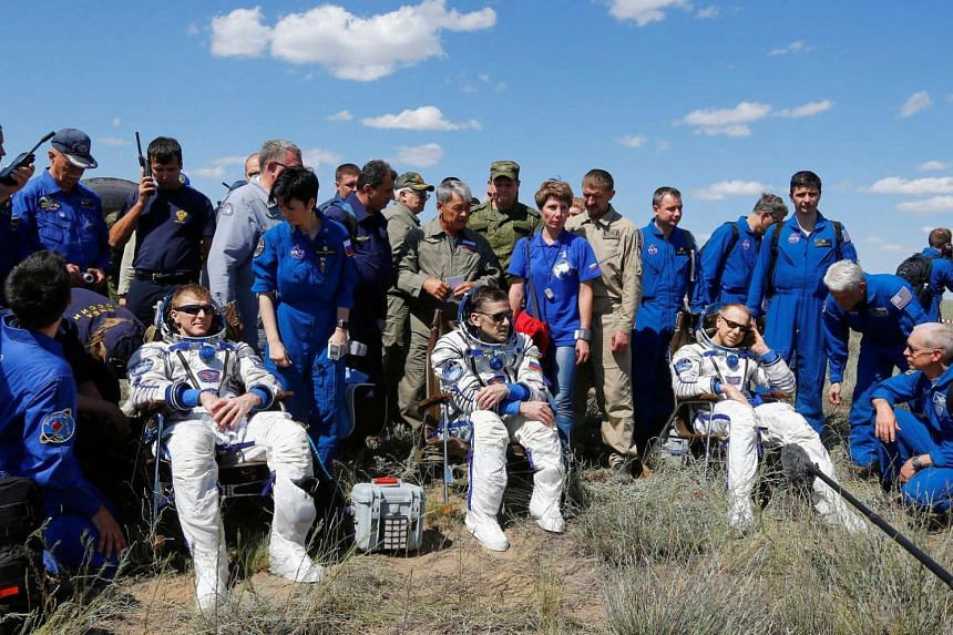 The astronauts, surrounded by ground personnel, resting after their safe landing in Kazakhstan.
