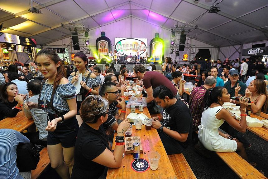 Above: RedDot BrewHouse's brewmaster Crystalla Huang Rui Qi, 25, holding up its signature craft beer infused with spirulina - the Monster Green Lager - at Beerfest Asia 2016 at the Marina Promenade yesterday. The brewery won the Best of Singapore awa