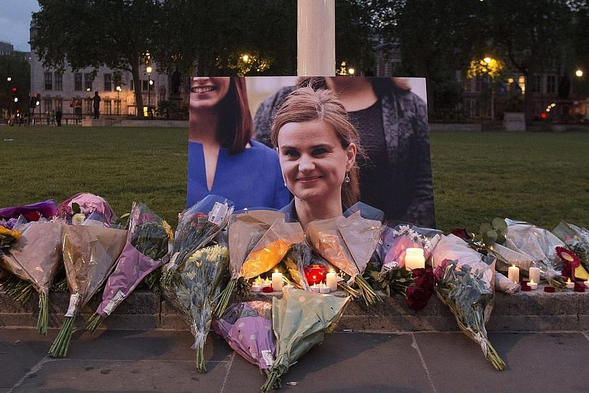 Floral tributes left in memory of Mrs Cox in Parliament Square, London, on Thursday. Mr Cameron has recalled Parliament on Monday to pay tribute to her.