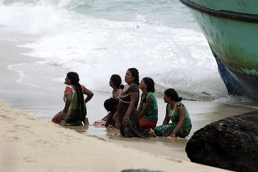 Some of the Sri Lankan migrants begging the Indonesian authorities for help yesterday as they knelt on Lhoknga Beach next to their boat.