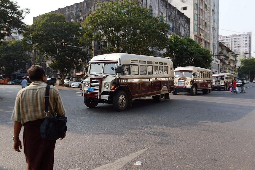 Period buses ferrying tourists around Yangon. By easing visa requirements for foreign travellers, Myanmar hopes to increase visitor arrivals and boost its tourism industry.