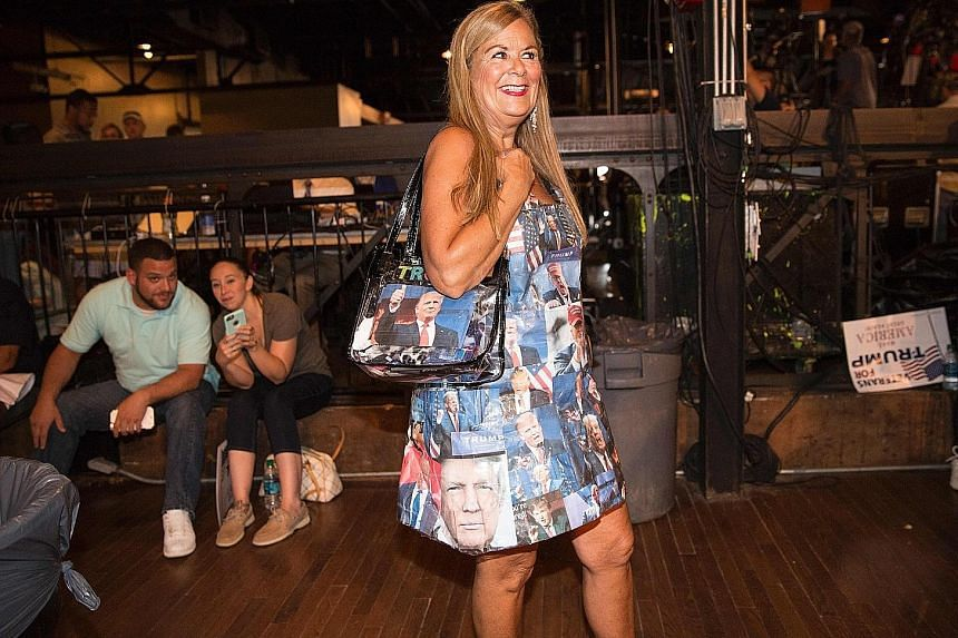 A supporter dresses the part, with her bag and outfit covered with images of Mr Trump, at a rally this week.