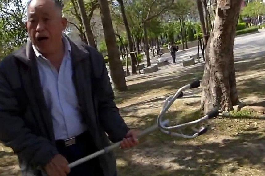 """A """"mainlander"""" elderly man waving his walking stick as he was harassed by citizen journalist Hung Su-chu. China-born Taiwanese often face discrimination from natives."""