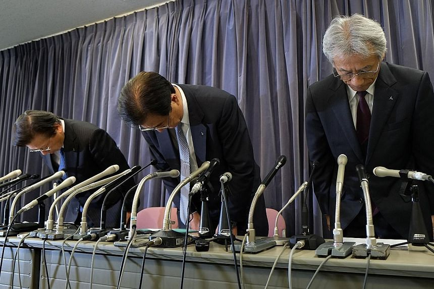 Top: The Mitsubishi headquarters in Tokyo, Japan. Above, from left: Mitsubishi Motors president Tetsuro Aikawa, chief executive Mr Masuko and executive vice-president Ryugo Nakao apologising during a press conference in Tokyo yesterday. The company s