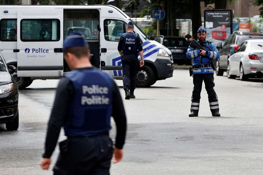 Belgian police officers standing guard near an apartment building during a reconstruction of the recent attacks, in the Brussels district of Etterbeek, on June 17.