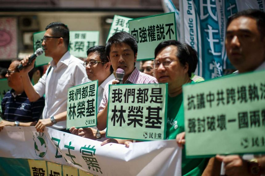 Democratic Party members holding up placards on their way to protest at the Chinese Liaison Office in Hong Kong on June 17.