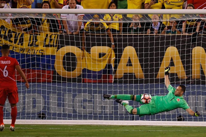 Colombian goalkeeper David Ospina stopping a penalty shot by Peru's Miguel Trauco.