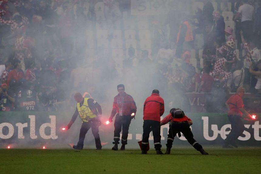 Ground staff removing flares from the pitch during the Euro 2016 match between the Czech Republic and Croatia.