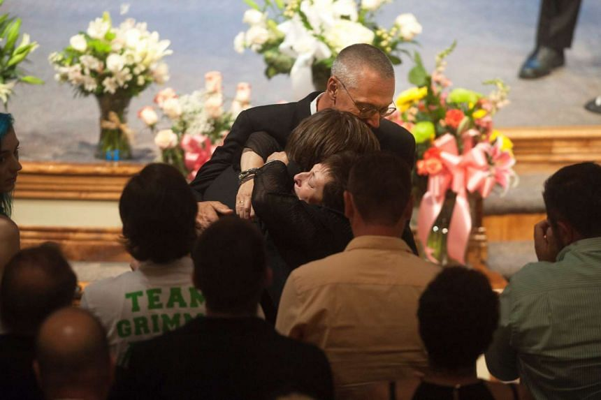 Tina and Bud Grimmie hugging their son Marcus during the memorial service.