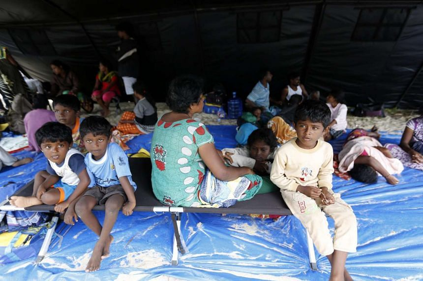 Sri Lankan migrants resting inside a tent at Lhok Nga beach in Aceh, Indonesia, on Saturday, June 18, 2016.