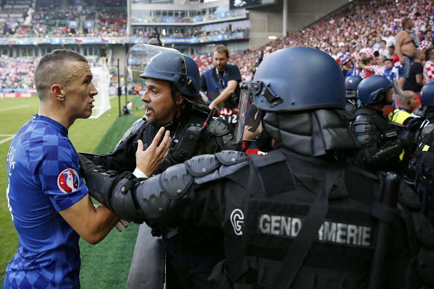 Croatia's Ivan Perisic (left) appeals to Croatia supporters after flares were thrown onto the pitch.