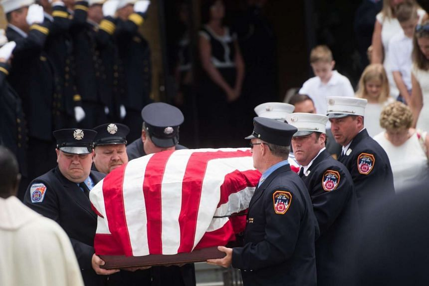 Pallbearers carrying the casket of Battalion Chief Lawrence Stack outside the Saints Philip and James Roman Catholic Church in New York on June 17.