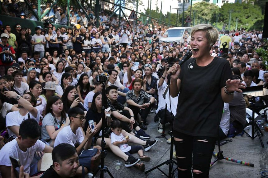 Cantopop singer Denise Ho (right) performs during a free concert in Hong Kong on June 19, 2016 after cosmetics giant Lancome cancelled a concert featuring the local singer who is critical of China.