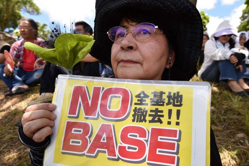 A demonstrator holds a placard during a rally against the US military presence in Naha, Okinawa prefecture on June 19, 2016.