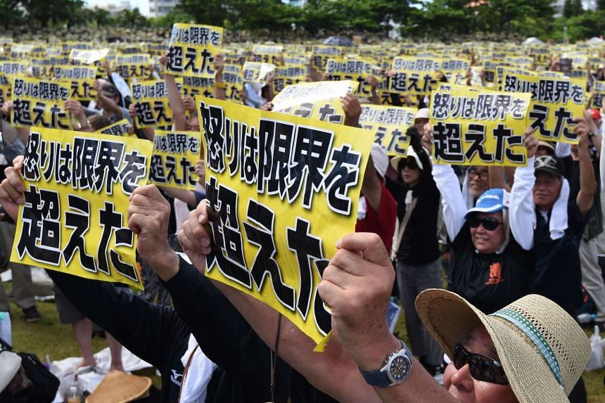 "Demonstrators hold placards that read ""our fury has gone beyond the limit"" during a rally against the US military presence in Naha, Okinawa prefecture on June 19, 2016."