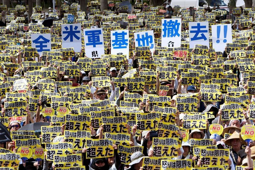 """Demonstrators hold placards that read """"our fury has gone beyond the limit"""" during a rally against the US military presence in Naha, Okinawa prefecture on June 19, 2016."""