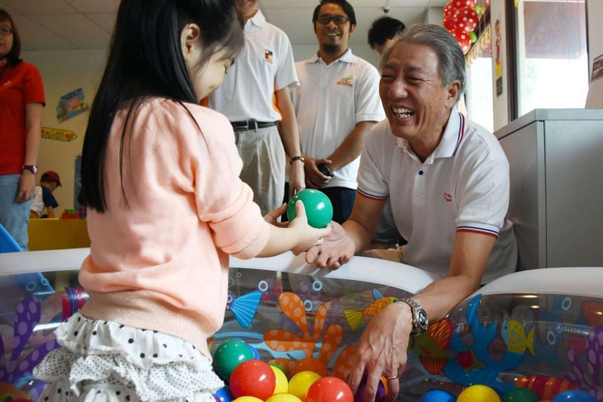 DPM Teo Chee Hean interacting with four-year-old Hazel New at North East Community Toy Library in Pasir Ris.