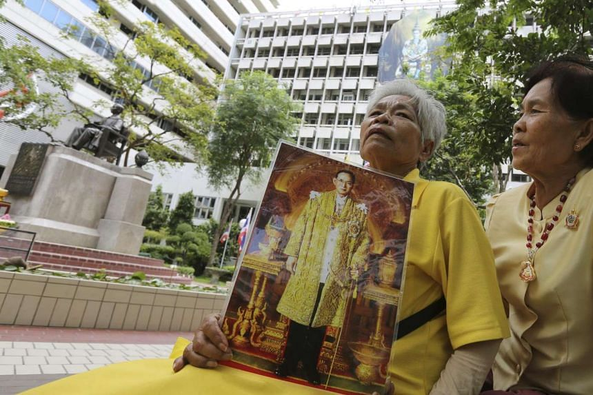 A well-wisher holds a photograph of Thai King Bhumibol Adulyadej as she prays for his health at the Siriraj Hospital in Bangkok on June 13, 2016.