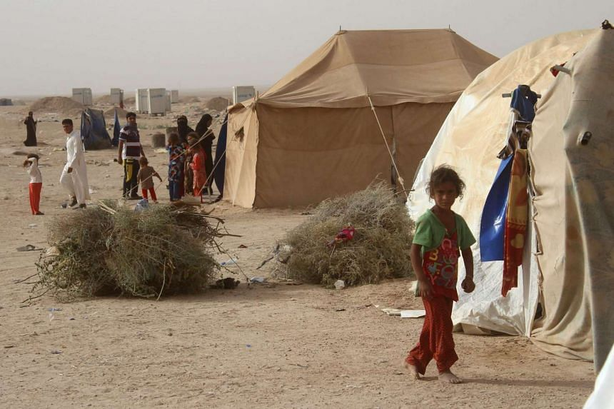 Displaced Iraqis from the embattled city of Fallujah stand outside tents where they are taking shelter some 18 kilometres from Ramadi on June 18, 2016.