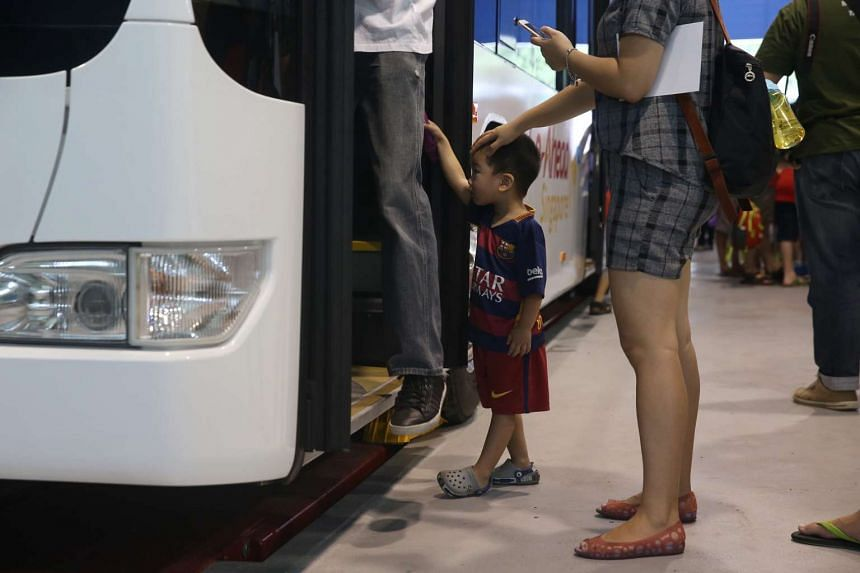 Three-year-old Jeremiah Cai waits for his turn to board and sit on the driver's seat of a single-deck bus at the Official opening ceremony of Go-Ahead Singapore's Loyang Bus Depot on June 19, 2016.