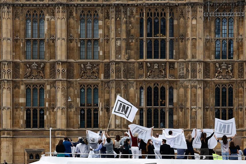 """A supporter of the UK Independence Party, which is campaigning for Britain's exit from the EU. Supporters of the """"Remain"""" campaign demonstrate on the deck of a boat outside the Houses of Parliament in London. A vote in favour of Brexit is expected to"""