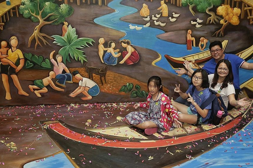 """The Chia family, comprising (from right) Mr Chia, his wife Madam Non, and daughters Yuan Ting, 13, and Kar Kar, 10, took """"a ride"""" at the 3D installation depicting the artwork, """"Life by the River"""" by local artist Liu Kang."""