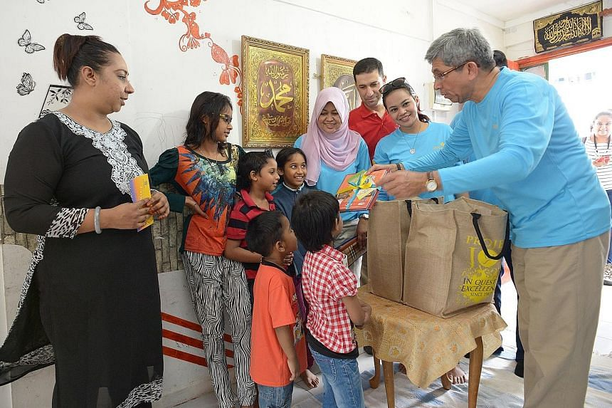 Left: Dr Yaacob presenting books and food items to Madam Zeenat (far left) and five of her six children yesterday, as part of Mendaki's annual charity drive. With Dr Yaacob are (from left) Mendaki CEO Tuminah Sapawi, Mr Necmettin Eskici, director of