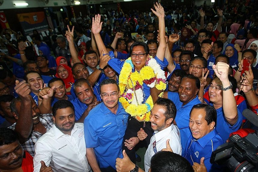 Mr Budiman celebrating after winning the by-election in Sungai Besar. He garnered 16,800 votes, beating the PAS contender's 6,902 votes and Amanah's 7,609. The winning margins for the ruling coalition in Sungai Besar and Kuala Kangsar were larger tha
