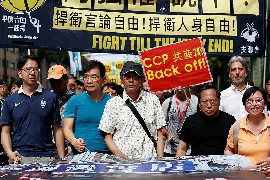 "Mr Lam (centre) participating in a protest march in Hong Kong yesterday against the Chinese authorities' ""white terror"" actions. Thousands of supporters joined in the protest, hailing his courage in going public with the account of his arrest and det"